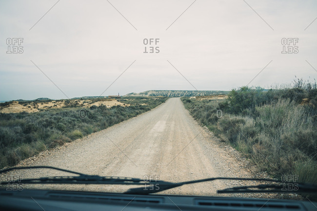 Empty road leading between fields with vegetation