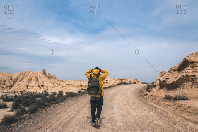 Back view of young man in yellow jacket and backpack walking on empty road stretchering high between stony hills in semi-desert Bardenas Reales Navarra Spain