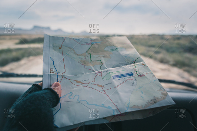 Man in car studying road map driving on road