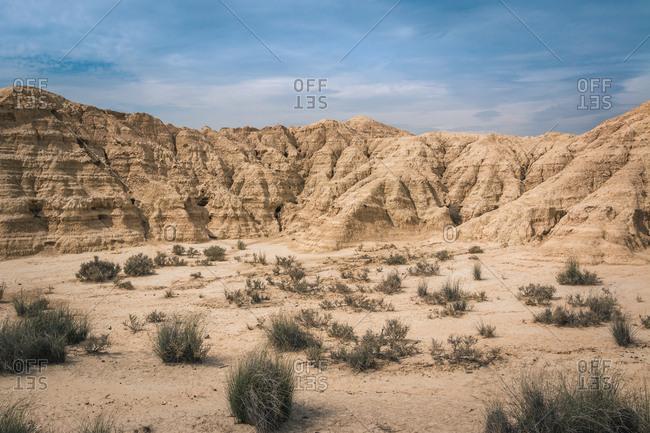 Breathtaking desert landscape with dry vegetation and yellow stony hills in semi-desert Bardenas Reales Navarra Spain