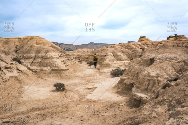 Man walking on amazing landscape of desert hills on background of blue sky