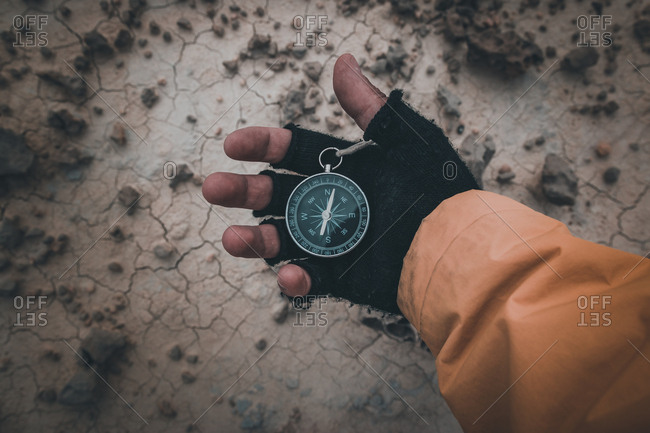 From above hand in black fingerless glove holding compass on desert place to find direction in semi-desert Bardenas Reales Navarra Spain