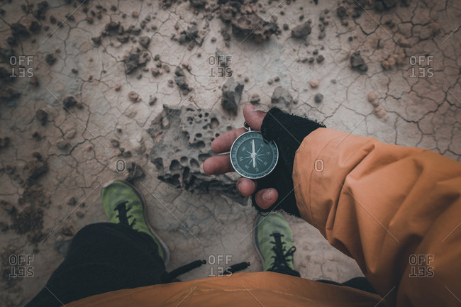 Compass in hand on dry desert area