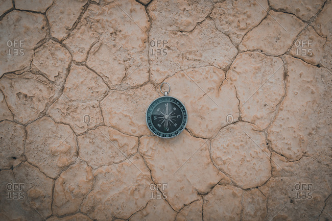Big compass on dry cracked desert area