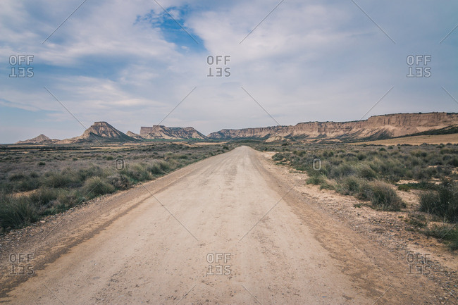 Dry desert road with mountains in the background