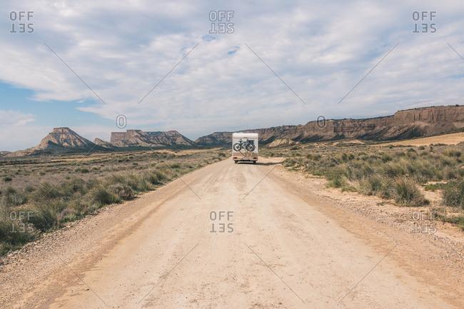 White trailer on empty road along desert
