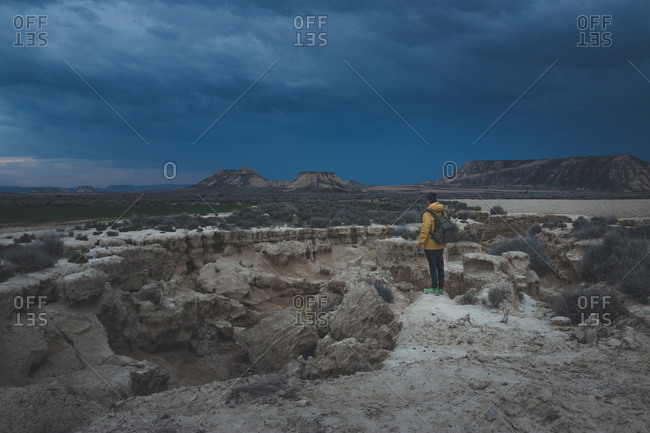 Side view of young man in yellow jacket and backpack standing on stone and looking at impressive blue sky in twilight in semi-desert Bardenas Reales Navarra Spain