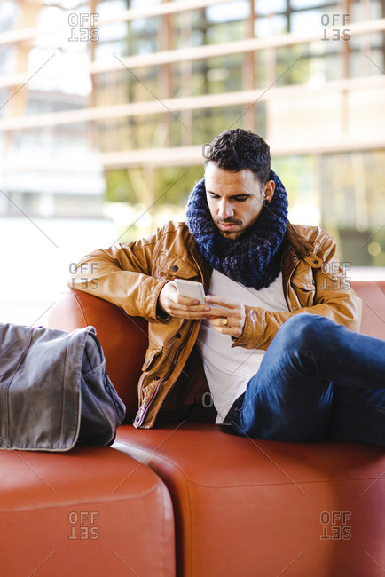 Male in trendy outfit browsing smartphone while sitting on comfortable leather sofa