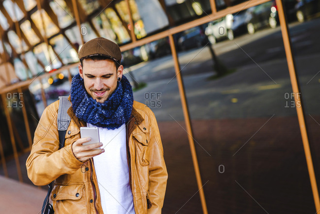 Trendy male in casual outfit using mobile phone while walking near glass wall of contemporary building