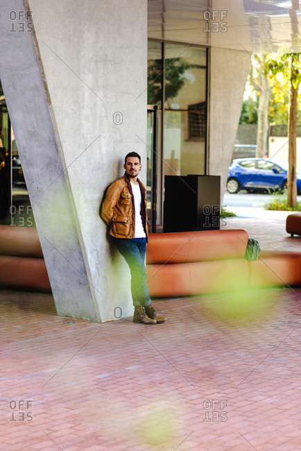 Confident trendy young guy leaning on concrete pillar near leather couch outside contemporary building on city street