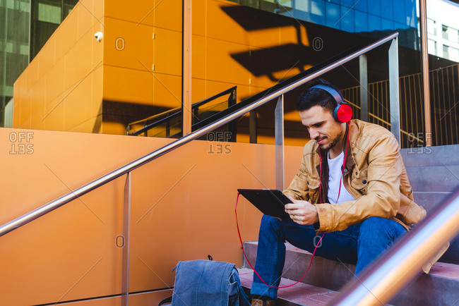 Handsome male in headphones listening to music and browsing tablet while sitting on stairs outside modern building