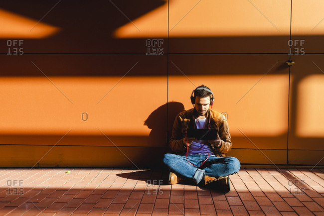 Handsome male in headphones listening to music and browsing tablet while sitting on stairs outside modern building on sunny day