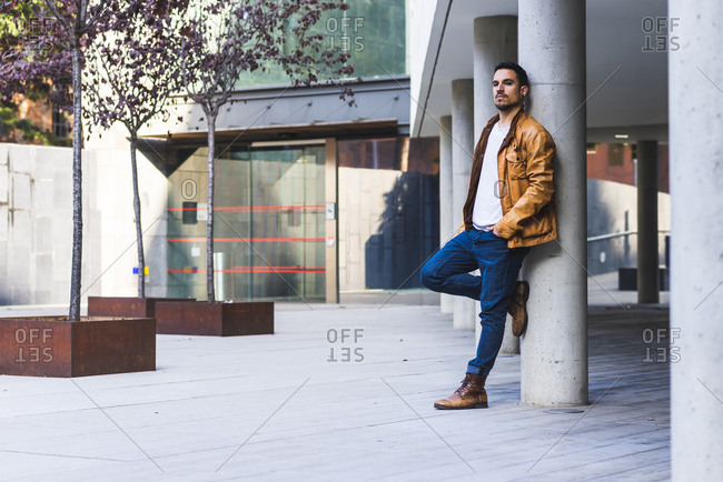 Side view of confident trendy young guy leaning on concrete pillar outside contemporary building on city street