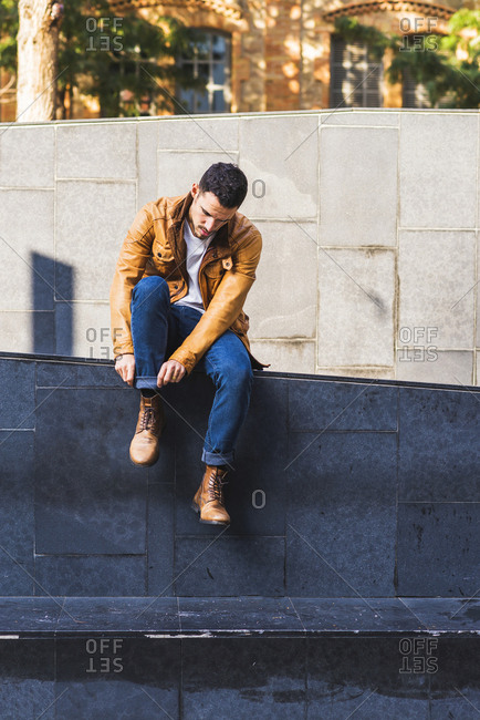 Confident trendy young guy sitting in concrete step outside contemporary building on city street