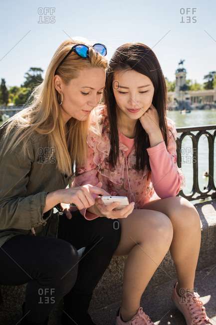 Young multiracial women in trendy outfits smiling and browsing smartphone while sitting near embankment railing on sunny day on city street
