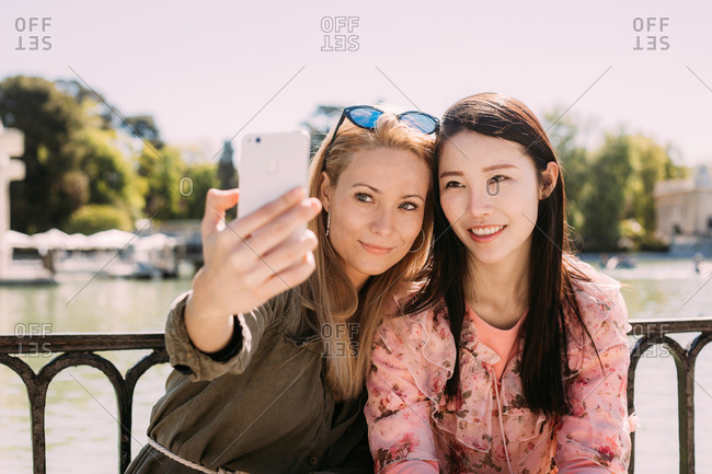 Young multiracial women in trendy outfits smiling and taking a selfie with smartphone while sitting near embankment railing on sunny day on city street