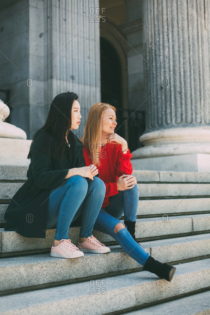 Stylish multiracial women looking away while resting on stairs of aged building on city street