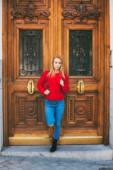 Positive young female in stylish outfit looking at camera while leaning on ornamental door of old building on city street