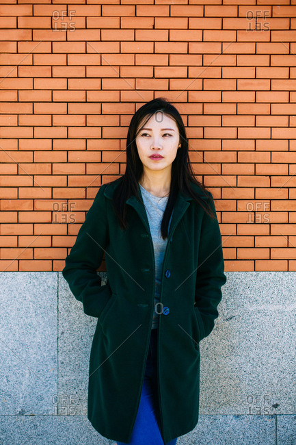 Pensive Asian female in trendy outfit and looking away while leaning on brick wall