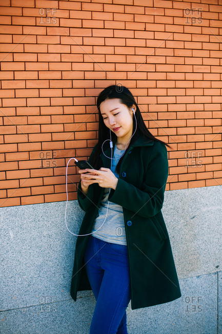 Young Asian woman listening to music and browsing smartphone while leaning on brick wall on city street