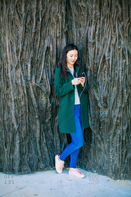 Beautiful Asian woman in stylish outfit listening to music and using smartphone while leaning on rough wall with relief of tree routs