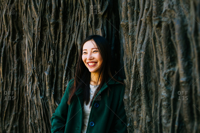 Excited Asian female in trendy outfit smiling and looking away while leaning on wall with relief of tree roots