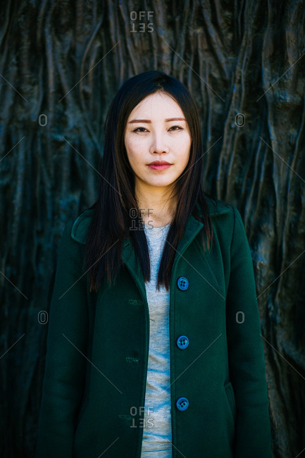 Pensive Asian female in trendy outfit smiling and looking away while leaning on wall with relief of tree roots