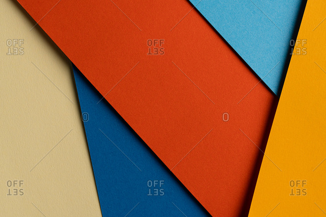 From above layout of colorful cardboard sheets in orange and blue shades
