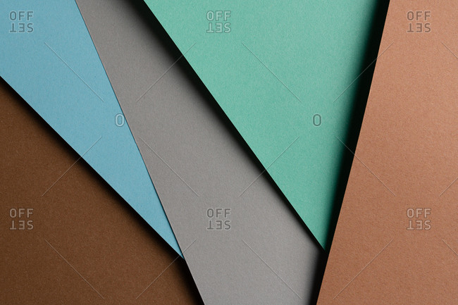From above layout of colorful cardboard sheets in brown, grey and blue shades