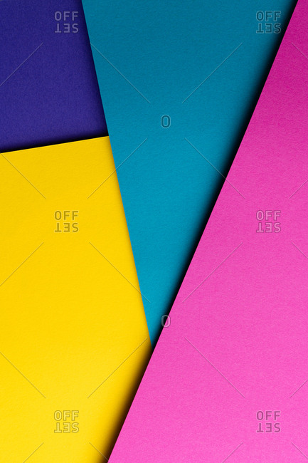 From above layout of colorful cardboard sheets in blue, purple, pink and yellow shades