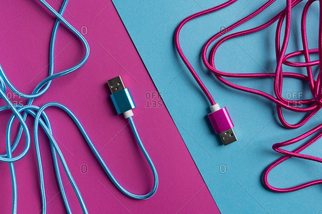 Top view of neon pink and blue colored USB cables on colorful cardboard background