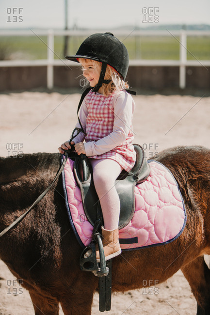 Cheerful small girl in dress and jockey hay sitting on horse while learning to ride on racetrack