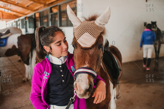 Little girl embracing with small pony in cute hat on ears standing inside of stable