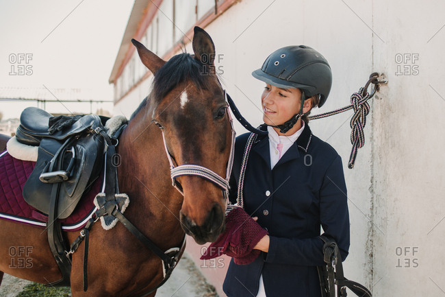 Side view of young teen woman in jockey helmet and jacket caressing horse standing together outdoors