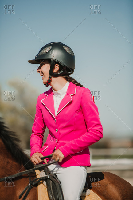 Close-up view of teenage jockey on horse riding on racetrack on a sunny day