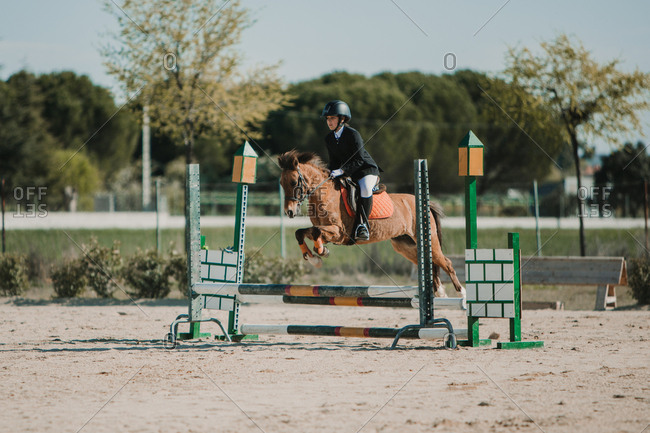 Side view of teenage jockey on horse leaping over horizontal wooden bars while riding on racetrack