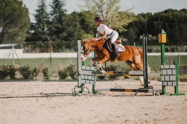 Teenage jockey on horse leaping over horizontal wooden bars while riding on racetrack