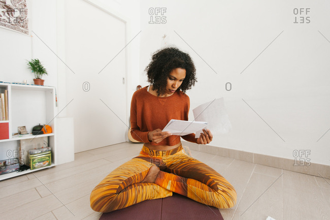 African American attractive young woman sitting in yoga pose with legs crossed and checking routine paper