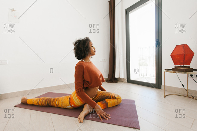 African American attractive young woman sitting in yoga pose with closed eyes on mat in light room