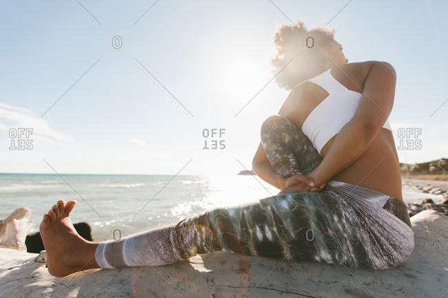 Side view of African American attractive young woman doing titibasana yoga posture by the beach