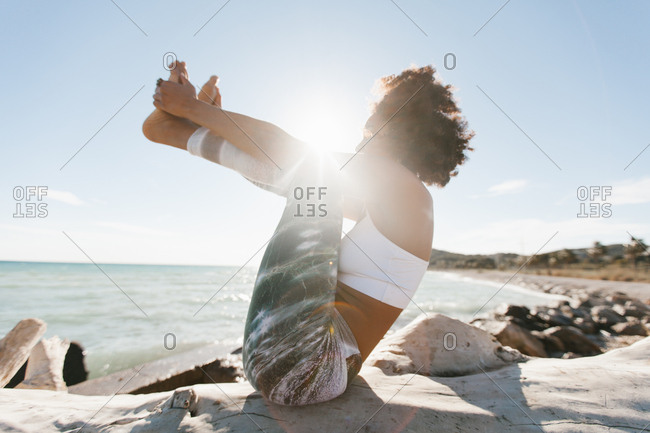 Side view of African American attractive young woman in yoga posture in open air on background of calm water in sunny day