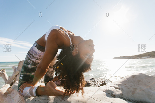 Side view of African American attractive young woman standing in yoga posture like bridge in open air on background of calm water in sunny day