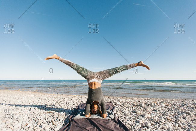 African American attractive young woman in yoga headstand posture and spreading out legs in open air on background of calm water in sunny day