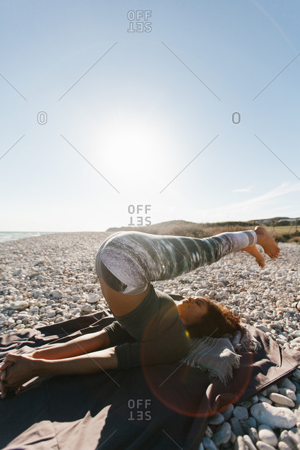 African American attractive young woman in yoga headstand posture in open air on background of calm water in sunny day