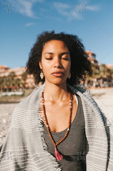 African American attractive young woman covered with grey plaid meditating in lotus yoga posture on sandy beach in bright day