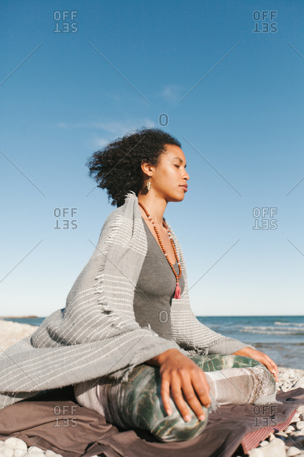 Side view of African American attractive young woman covered with grey plaid meditating in lotus yoga posture on sandy beach in bright day