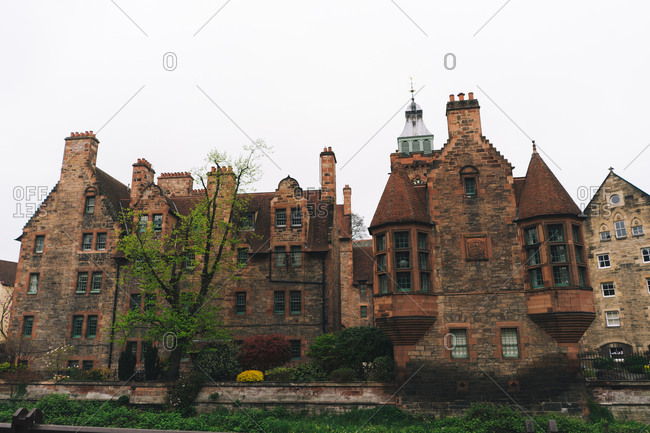 Landscape of old masonry buildings flowing among green bushes, Scotland