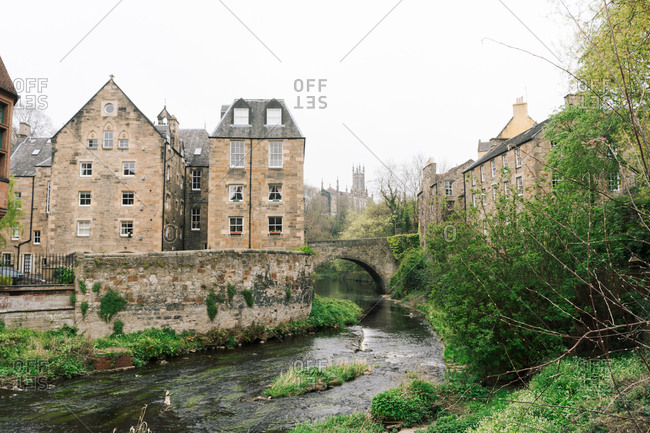Landscape of old masonry buildings with shallow river flowing among green bushes, Scotland