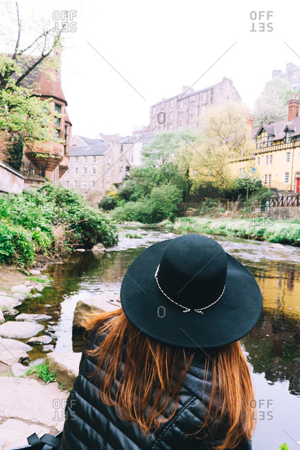 Back view of woman in hat contemplating landscape of old masonry buildings with shallow river flowing among green bushes, Scotland