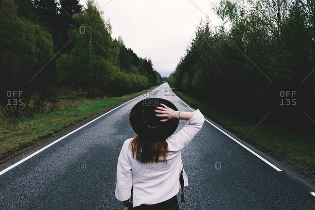 Back view of trendy woman in black hat standing in solitude on remote road with lush green trees, Scotland